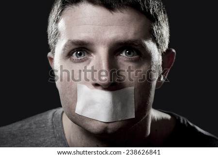 attractive young man with mouth and lips sealed on tape to prevent from speaking free keeping him mute and censored in freedom of speech and expression concept close up eyes isolated on black - stock photo