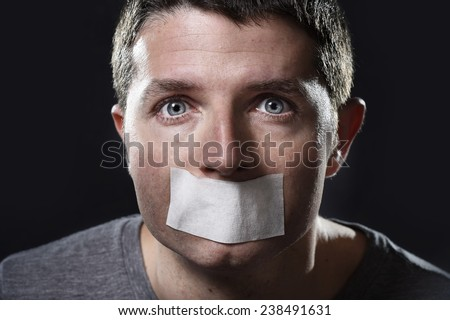 attractive young man with mouth sealed on duct tape to prevent him from speaking keeping him mute and censored in freedom of speech and expression concept isolated on dark grunge studio light style - stock photo
