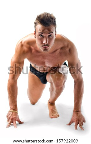 Attractive young man with muscular naked body ready to sprint and run