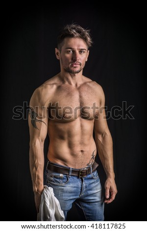 Attractive young man with naked muscular torso, wearing jeans - stock photo