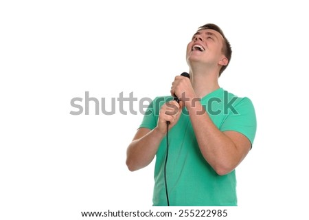 Attractive young man with positive emotions and energy is singing into the microphone. - stock photo