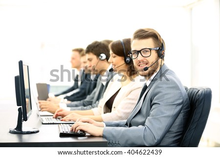 Attractive young man working in a call center with his colleagues - stock photo