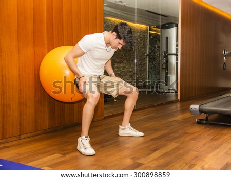Attractive young man working out with exercize ball against wall to train abs