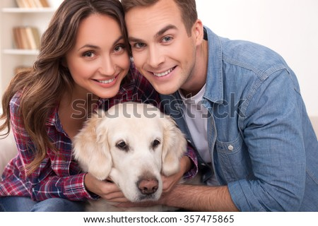 Attractive young married couple is playing with dog at home. They are sitting on sofa and embracing the animal. The man and woman are looking at camera and smiling - stock photo