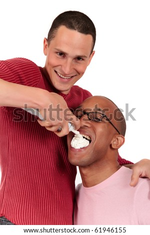 Attractive young mixed ethnicity gay, homosexual couple, Caucasian and African American eating whipped cream.  Studio, white background. - stock photo