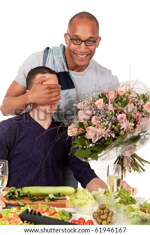 Attractive young mixed ethnicity gay, homosexual couple, Caucasian and African American in kitchen, celebrating valentine at the dinner table.  Studio, white background. - stock photo