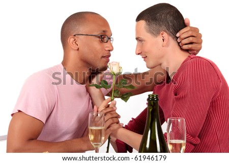 Attractive young mixed ethnicity gay, homosexual couple, Caucasian and African American in kitchen, celebrating valentine with champagne and flower.  Studio, white background. - stock photo