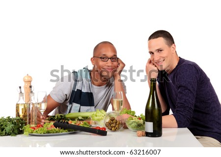 Attractive young mixed ethnicity gay, homosexual couple, Caucasian and African American in kitchen, preparing salad for dinner.  Studio, white background. - stock photo