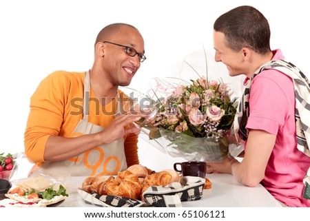 Attractive young mixed ethnicity gay, homosexual couple, Caucasian and African American in kitchen, celebrating Valentine at the breakfast table.  Studio, white background. - stock photo