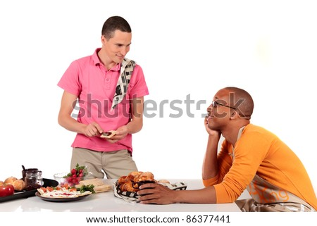 Attractive young mixed ethnicity gay, homosexual couple, Caucasian and African American in kitchen, preparing breakfast.  Studio, white background. - stock photo