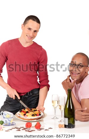 Attractive young mixed ethnicity gay, homosexual couple, Caucasian and African American in kitchen, enjoying a fruit pie and  champagne.  Studio, white background. - stock photo