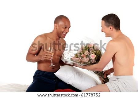 Attractive young mixed ethnicity gay, homosexual couple, Caucasian and African American men in the bedroom,  celebrating valentines day with champagne and bouquet flowers.  Studio, white background. - stock photo