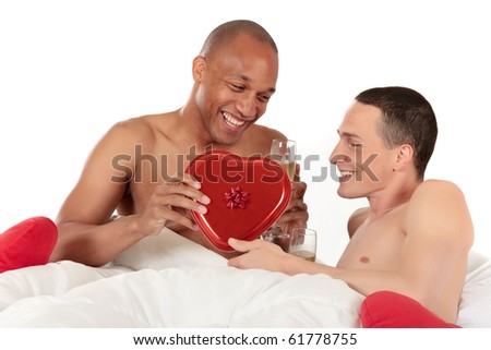 Attractive young mixed ethnicity gay, homosexual couple, Caucasian and African American men in the bedroom, grooming, celebrating valentines day.  Studio, white background. - stock photo