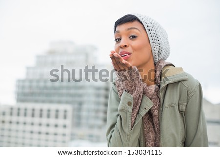 Attractive young model in winter clothes blowing a kiss to the camera outside on a cloudy day - stock photo