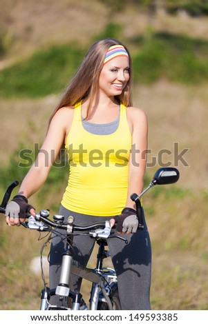 Attractive young model on bicycle standing on road. Cycle gear for cyclist trains for fitness.