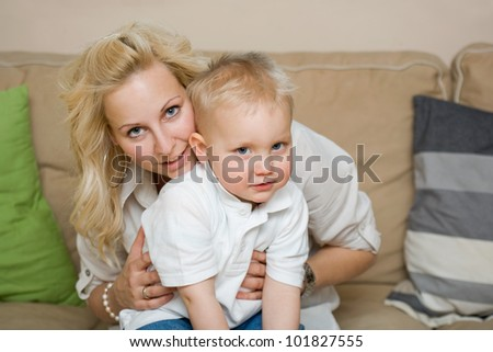 Attractive young mother and cute son having fun indoors at home. - stock photo