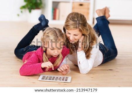 Attractive young mother and her cute little daughter lying on their stomachs on the floor playing with a tablet computer - stock photo