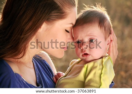 attractive young mother and newborn baby on beautiful, sunset
