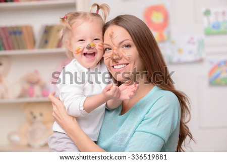 Attractive young mother is holding her daughter and embracing. They are looking at camera and laughing. The woman and girl have colored paint on their faces - stock photo