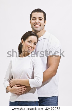 Attractive young multi-ethnic couple standing together and hugging. Vertically framed photo. - stock photo