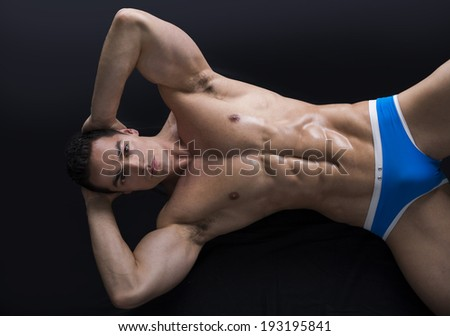 Attractive young muscle man laying on the floor with muscular ripped body - stock photo