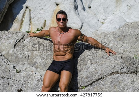 Attractive young muscle man shirtless against white rocks - stock photo