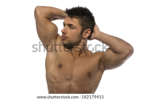 Attractive young muscle man showing athletic torso and biceps, hands behind his head - stock photo