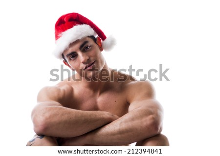 Attractive young muscle man sitting and smiling with muscular ripped body in Santa Claus's red hat - stock photo