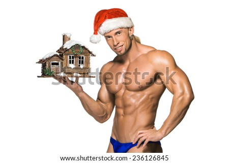 Attractive young muscle man smiling with muscular body in Santa Claus's red hat, isolated on white background - stock photo