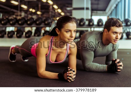 Attractive young muscular man and woman doing plank exercise while working out in gym - stock photo