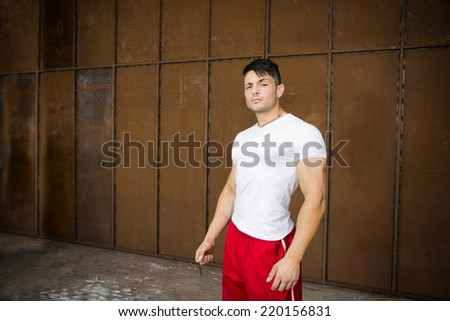 Attractive young muscular man portrait in white shirt and red gym suit pants posing - stock photo