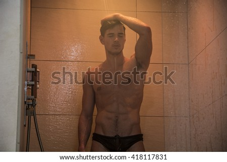Attractive Young Muscular Man Taking Shower - stock photo