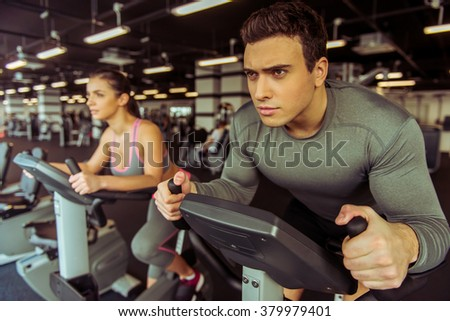 Attractive young muscular people working out on an exercise bike in gym - stock photo