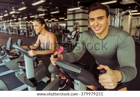 Attractive young muscular people working out on an exercise bike in gym and smiling - stock photo