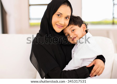 attractive young muslim woman sitting on couch with her son - stock photo