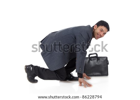 Attractive young nepalese businessman with suitcase kneeling,  ready for race. Start position. Studio shot. White background.