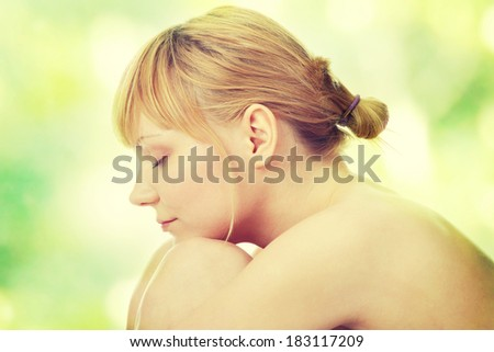 Attractive young nude woman getting ready for spa treatment, against abstract green background - stock photo