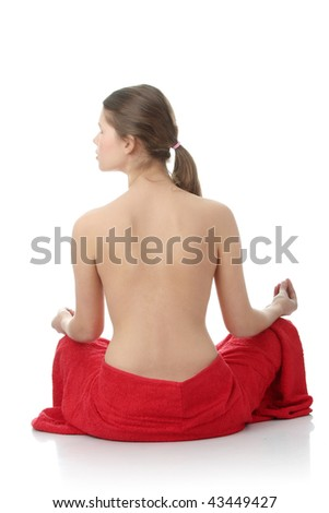 Attractive young nude woman in lotus position getting ready for spa treatment, isolated on white