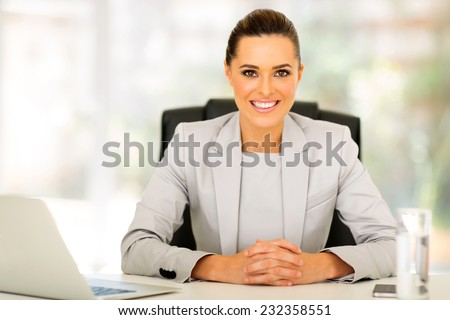 attractive young office worker sitting in office - stock photo