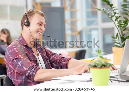 Attractive young operator is typing on laptop in open office. He is sitting at desk and laughing. The man is wearing headphones and talking into microphone - stock photo