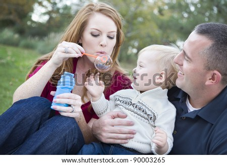 Attractive Young Parents Having Fun Blowing Bubbles with their Child Boy in the Park. - stock photo