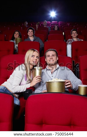 Attractive young people are watching movies in cinema - stock photo