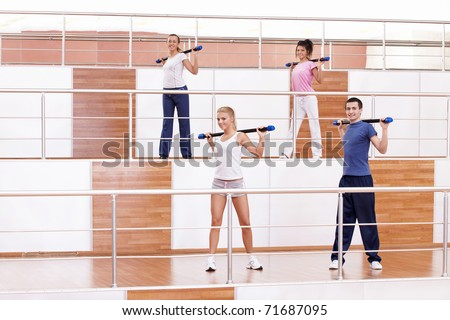 Attractive young people doing exercises in the fitness club - stock photo