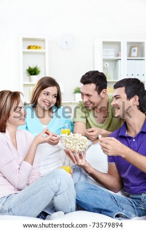 Attractive young people eating popcorn - stock photo