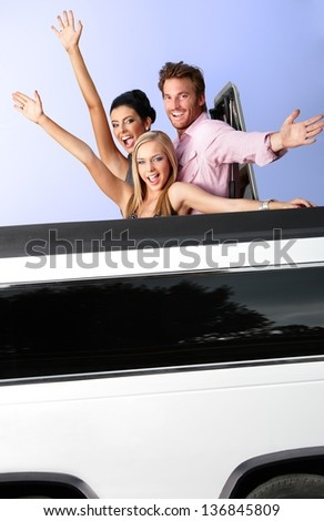 Attractive young people having fun in limousine, waving.