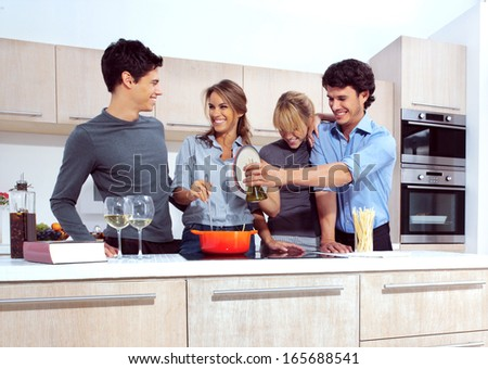 Attractive young people in the kitchen  - stock photo