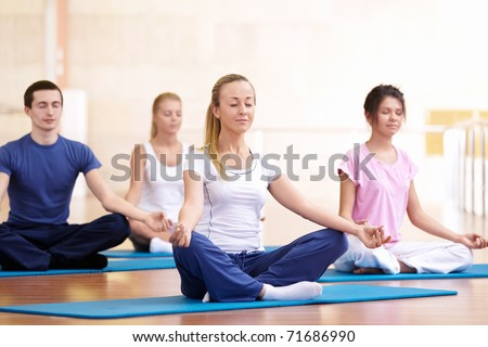 Attractive young people meditate - stock photo