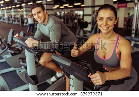 Attractive young people working out on an exercise bike in gym and smiling. Woman showing OK sign - stock photo
