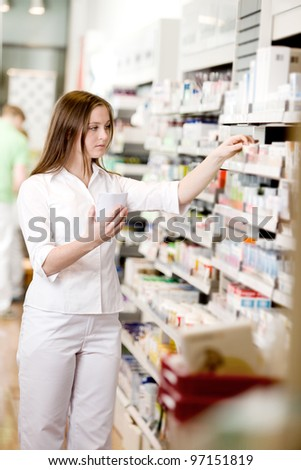 Attractive young pharmacist filling prescription - stock photo