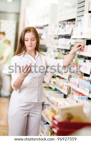 Attractive young pharmacist in pharmacy looking at prescription - stock photo